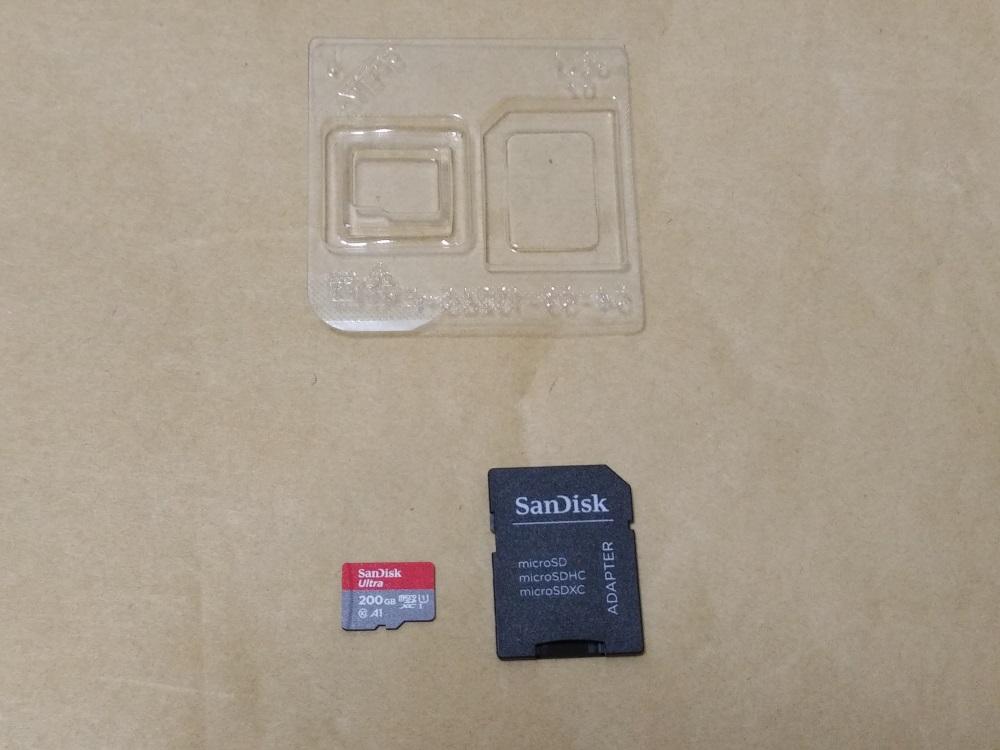 サンディスク SDSQUAR-200G-GN6MAのプラケースからアダプターとmicroSDカードを取り出した様子